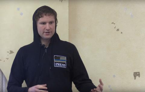 Agent Reid Ross holding a press conference about John Zerzan's sex robots