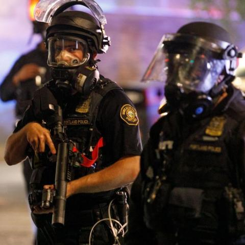 Portland, Oregon police officers confront protesters on the evening of July 4.