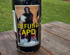 A glass bottle with a sticker of a cop in riot gear holding a pack of leaking water bottles?